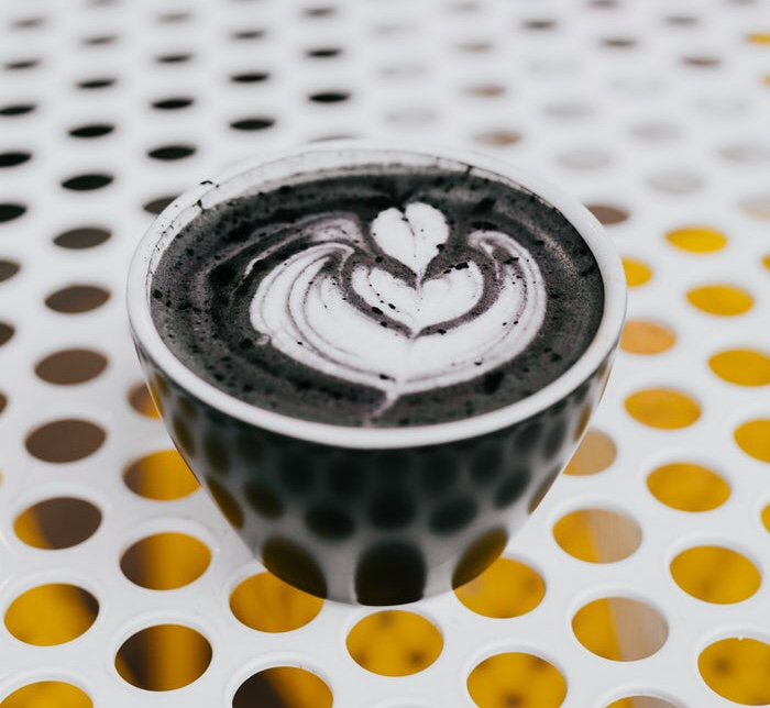 A charcoal latter in a black cup sits on a white table.