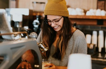 A smiling barista in a grey shirt and yellow beanie makes drinks.