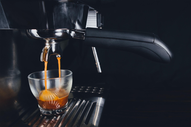 An espresso shot brews into a glass cup.