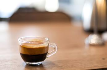An espresso in a double-walled glass cup on a wooden table.