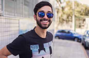 A barista in blue sunglasses looks proudly at the camera and smiles.