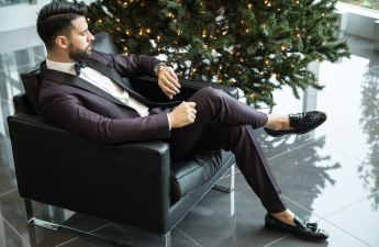 A man in a suit sitting on a couch looks at his watch impatiently.