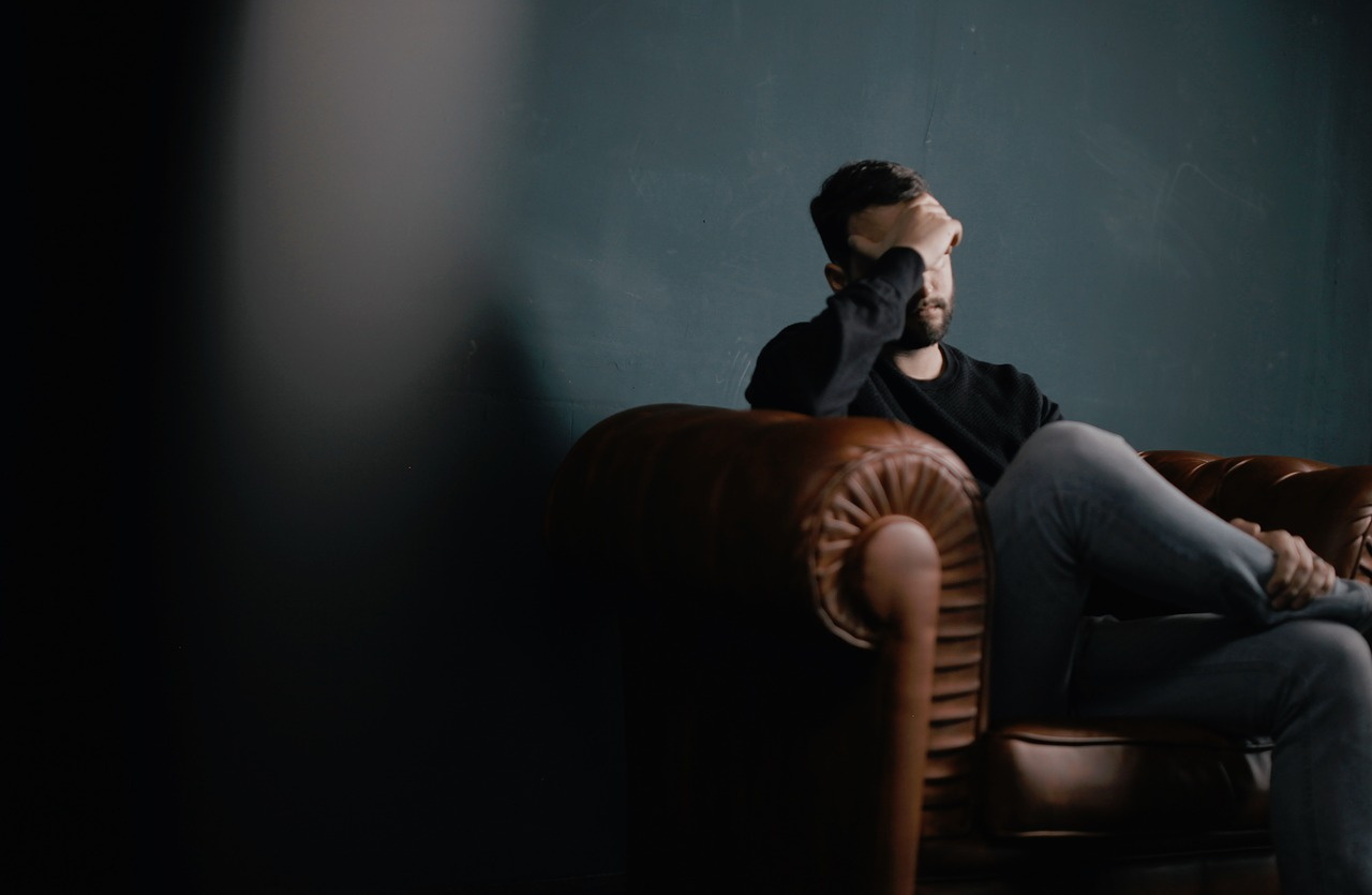 A man sits on an oxblood couch, contemplating.