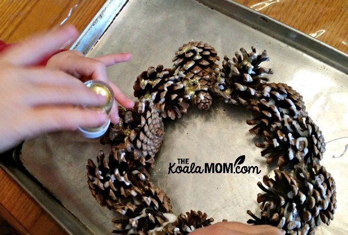 Applying glitter to a pine cone wreath