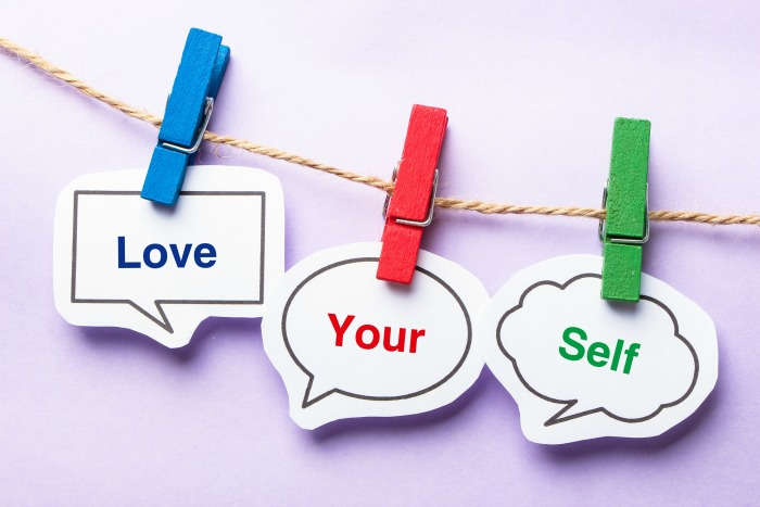 Love your self paper bubbles with clip hanging on the line against purple background.