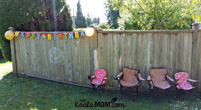 Our outdoor birthday party: happy birthday sign on the fence and lawn chairs to relax in
