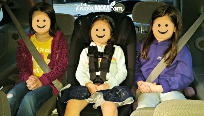 Three girls sitting in their car seats and booster seats in a Dodge Caravan