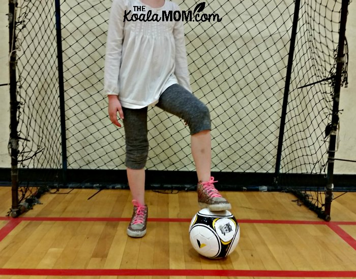 Girl standing in a soccer net with her foot on a Sportball soccer ball during one of their kids sports classes.