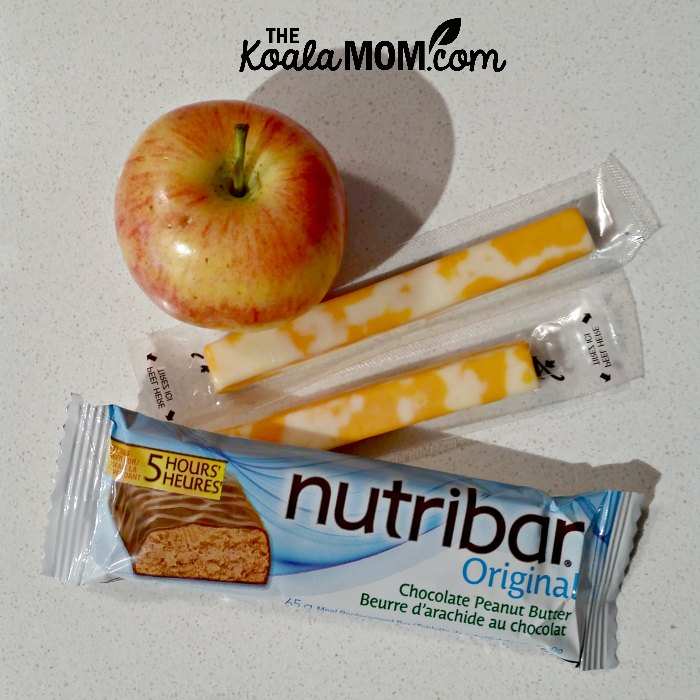 Some healthy snacks - a Nutribar, apple, and cheese sticks