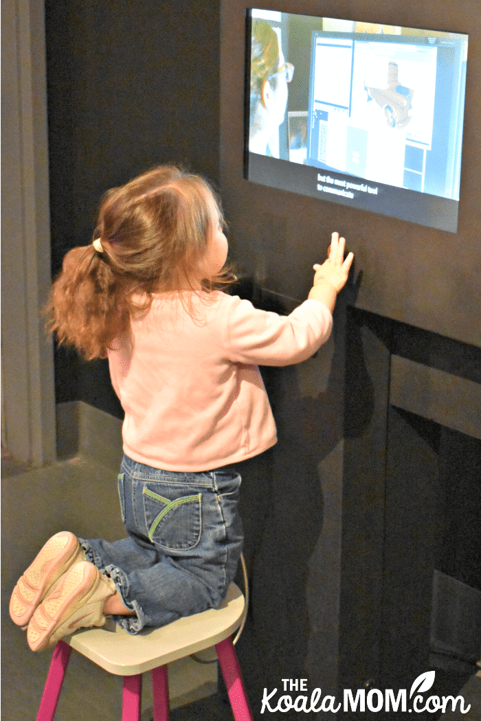 A toddler watches a Pixar interview at the Science Behind Pixar Exhibit.