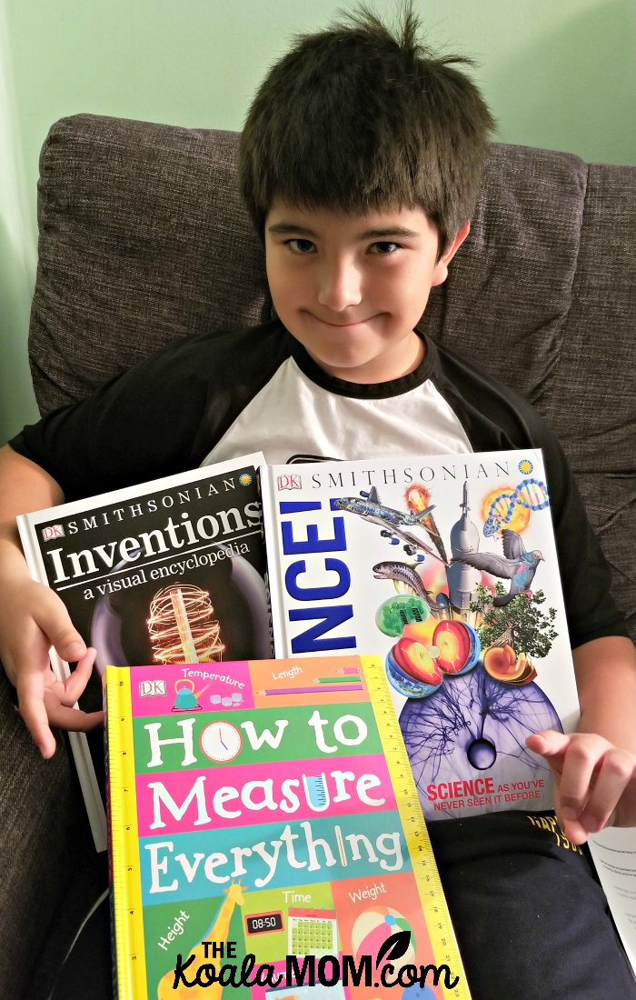 Boy holding three DK books that make science exciting - How to Measure Everything, Inventions: a Visual and Encyclopedia, and Discover Science!