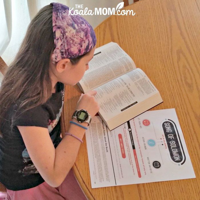 Sunshine reading her Bible with a printable reference sheet from Teaching Sunday School.