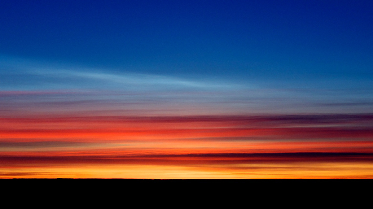 Stratospheric Cloud lit by a rising sun coloring the sky in long trails of deep orange, red, purple and blue.