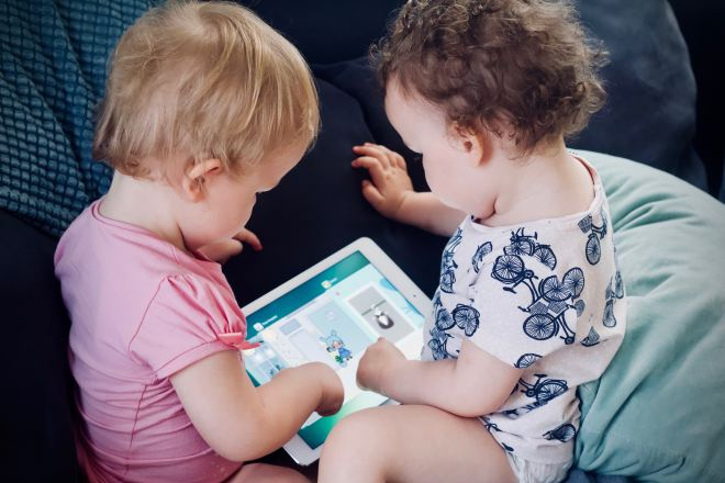 Two toddlers playing with tablet.