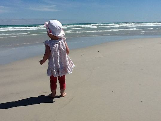 "Adrianna's daughter ""Squishy"" walking along a beach in Australia – Photo by Adrianna Granville"