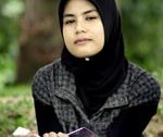 Muslim student wears the hijab while reading a book.
