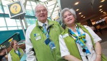"Benno ""Ben"" Ganz (left) standing beside fellow Green Coat volunteer at YVR. Photo by Elton Hubner."