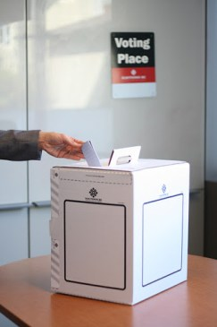 A voter exercises his or her right to vote, by dropping a ballot into the ballot box. - Photo courtesy by Elections BC.