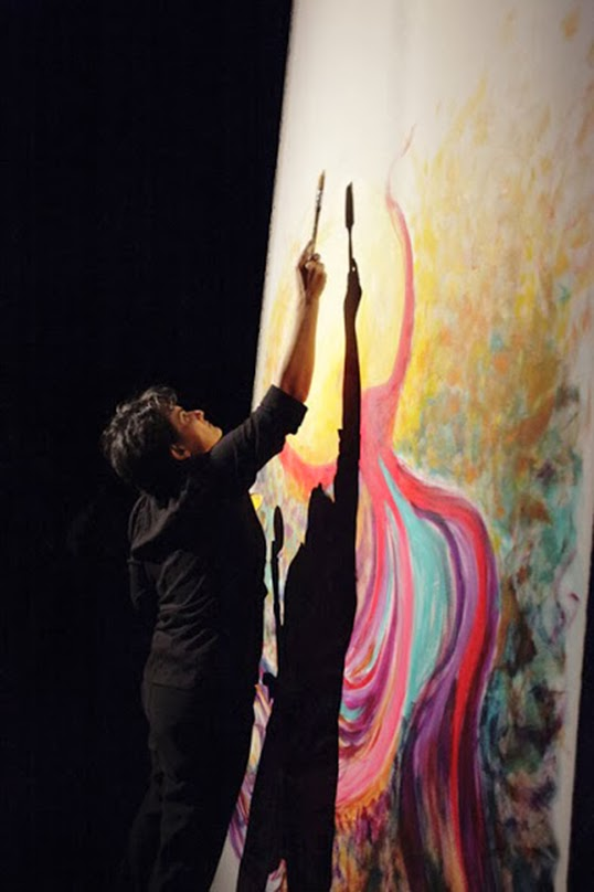 Artist NikNaz painting Survive at an event called Anu.