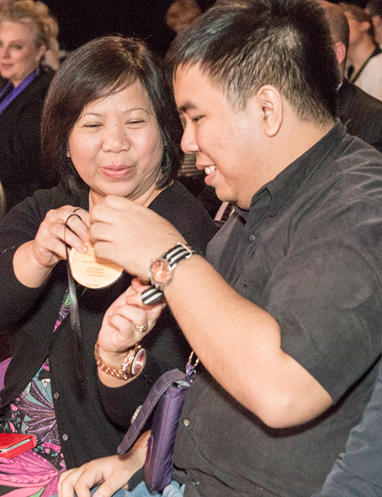Catherine Cham helps her son Vico Cham put on his 2015 ANCA world ambassador's pendant for his efforts to increase awareness of Autism in the Philippines. | Photo courtesy of UANCA Foundation