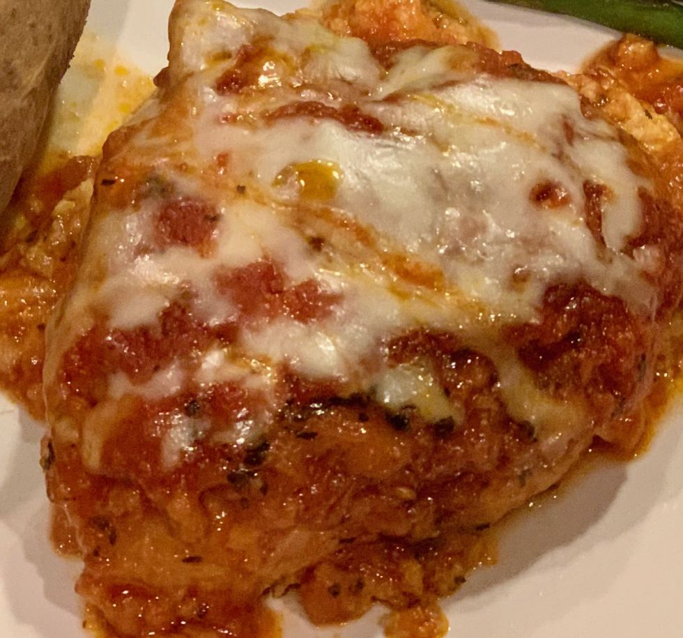 Close up of chicken parmesan with sauce and cheese melted on top