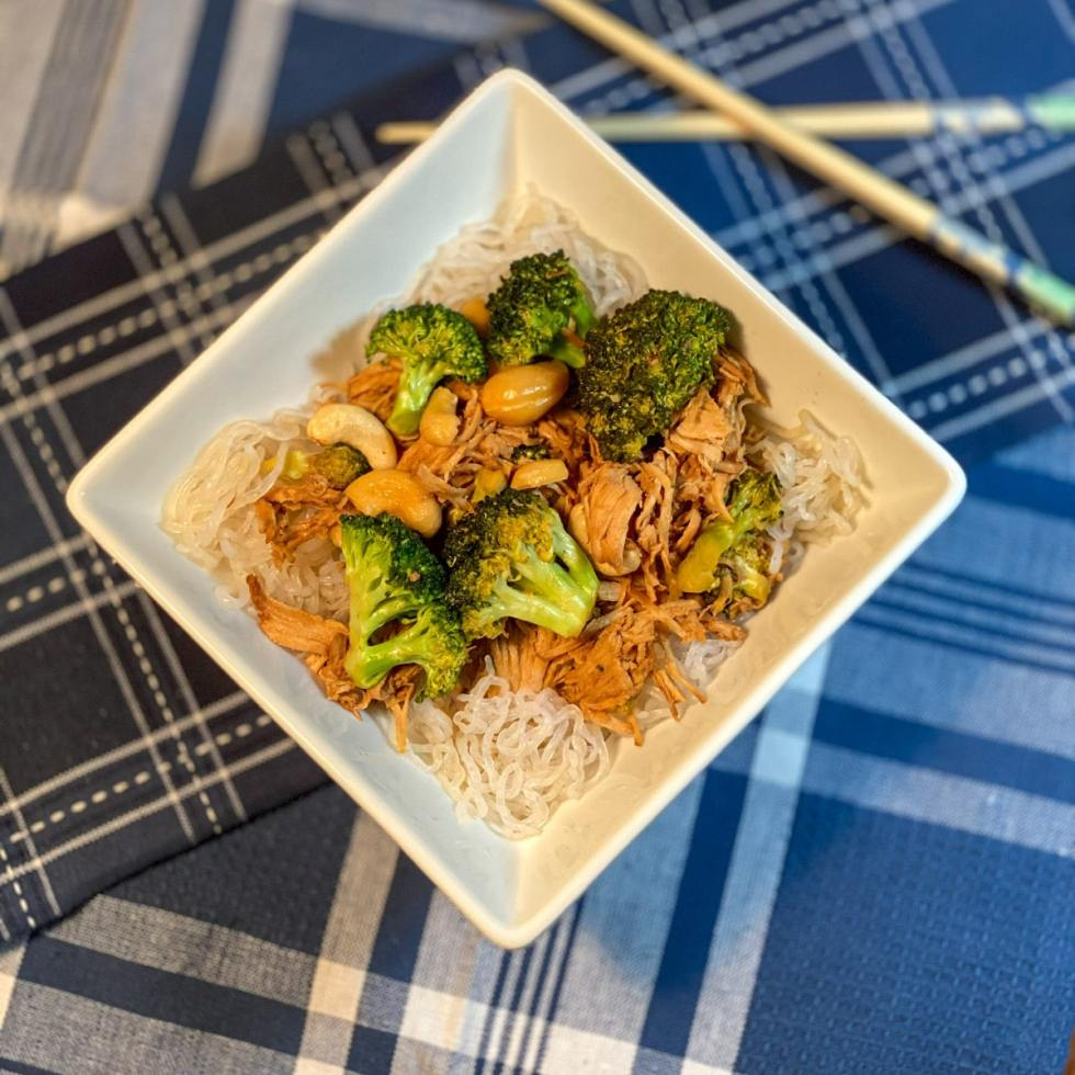 Top view of a diamond shaped bowl containing broccoli and chicken and cashew nuts with chop sticks in the background.