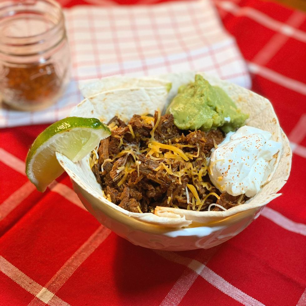 Close up of a soft taco bowl filled with shredded beef, sour cream, guacamole and shredded cheese with a lime wedge.