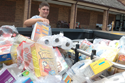 Leaven photo by Jill Ragar Esfeld St. James Academy freshman Jake Thies, a member of Holy Trinity Parish in Lenexa, adds another bag of groceries to the donations he helped collect for Catholic Charities food pantry.