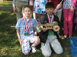 Sixth-graders AJ Brady and Minh Nguyen show off their mousetrap vehicle, which won first place at the Science Olympiad in Wichita.