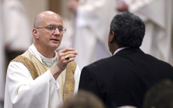 Bishop Edward J. Weisenburger of Salina distributes Communion during his May 1 episcopal ordination and installation Mass at Sacred Heart Cathedral in Salina. By Karen Bonar.