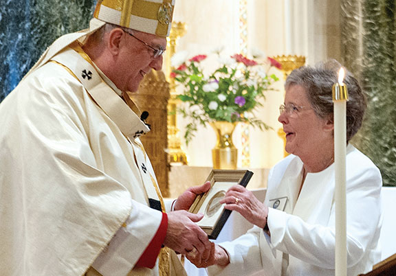PHOTO BY ROX STEC Sister Anne Shepard, prioress of the Benedictine Sisters of Mount St. Scholastica in Atchison, presents Archbishop Joseph F. Naumann with a plaque featuring the image of St. Scholastica as a token of appreciation.