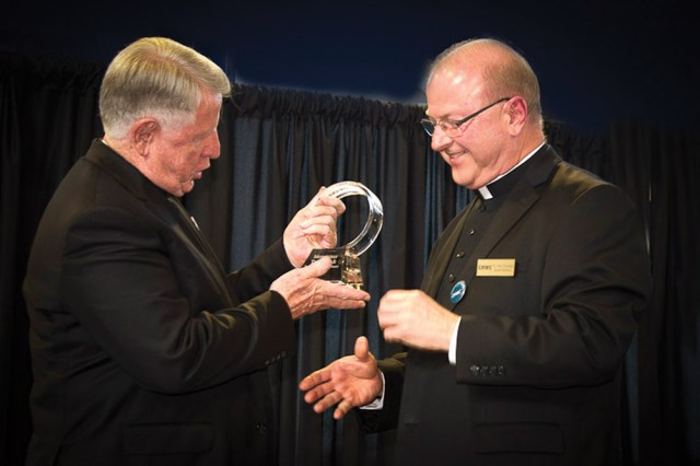 Photo by John Caulfield Father Gary Pennings (right), archdiocesan vicar general, hands Msgr. Thomas Tank with the first-ever Msgr. Thomas Tank Award from Community Housing of Wyandotte County. The award, which is expected to be presented annually, was presented at the Center Circle fundrasing event June 15 at Livestrong Sporting Park in Kansas City, Kan.