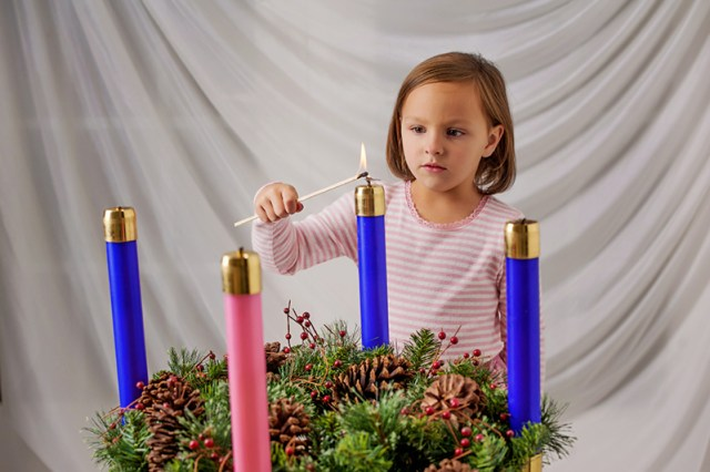 Mary Nearmyer, 5, lights the first candle on the traditional Advent wreath. Mary is the daughter of Deacon Dana and Debbie Nearmyer, members of Holy Trinity Parish, Lenexa. Advent begins on Nov. 29. Photo by Lori Wood Habiger