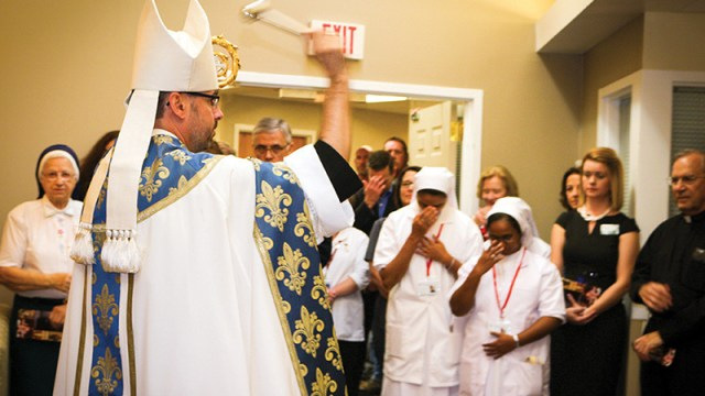 Abbot James Albers, OSB, blesses the newly dedicated St. Benedict and St. Scholastica Memory Care Neighborhood at Villa St. Francis in Olathe.