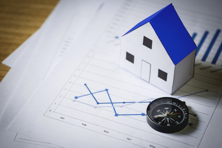 House model and compass on plan background, Real estate concept
