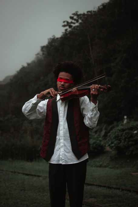 black blindfolded musician performing playing violin in nature