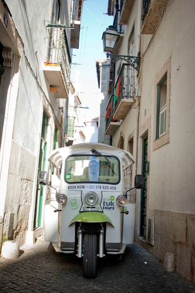 A Tuk Tuk squeezes through historic Lisbon
