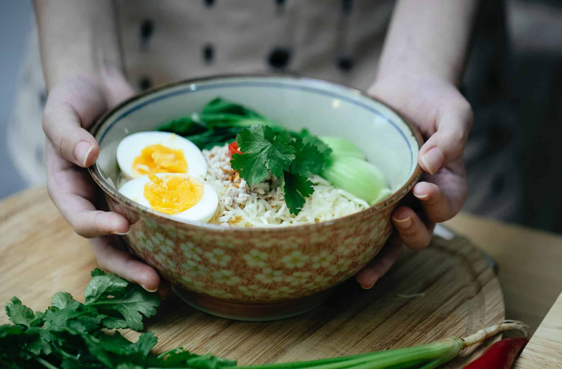 crop unrecognizable woman touching bowl with traditional ramen soup