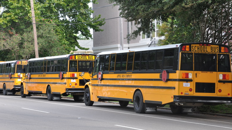 Buses line up at John Dibert Community School near City Park.