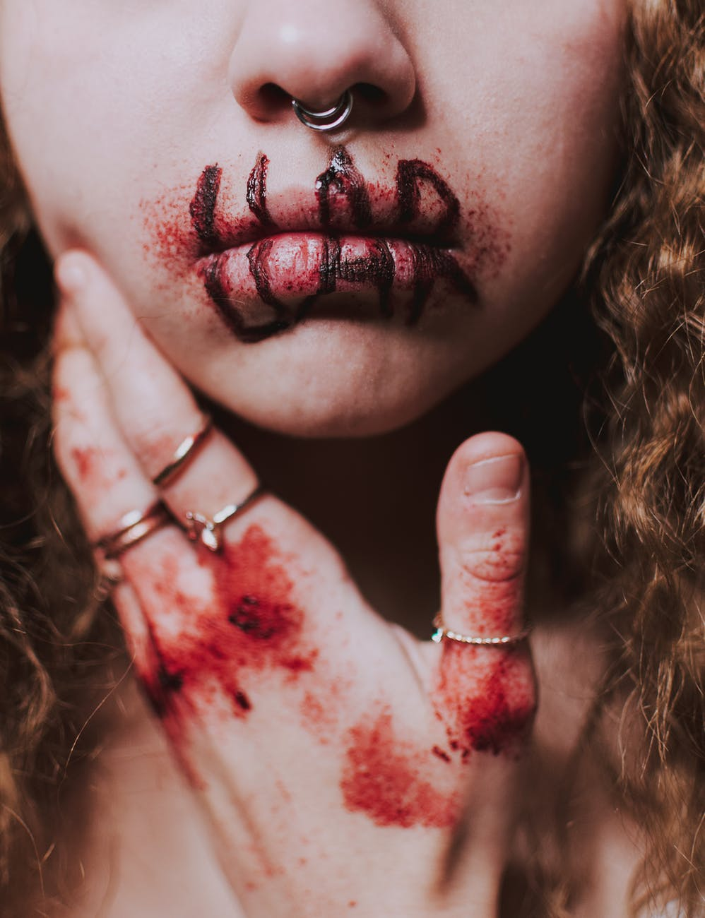 unrecognizable woman with bloody wounds with word liar on lips