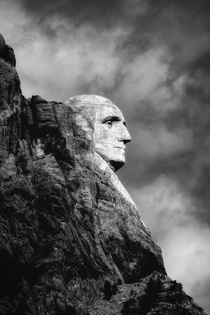 grayscale photo of mans face concrete statue