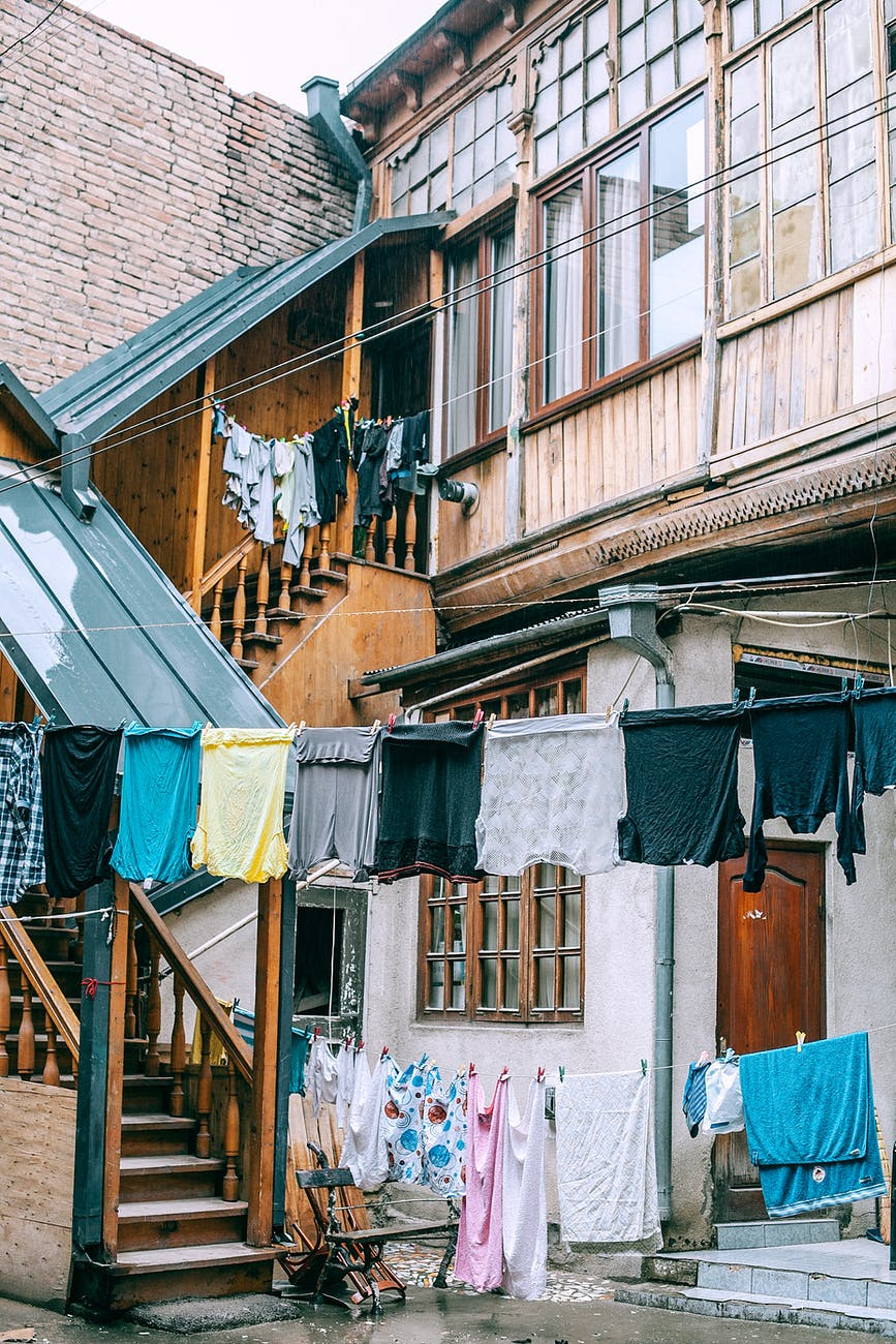 laundry drying on clothesline outside shabby poor house