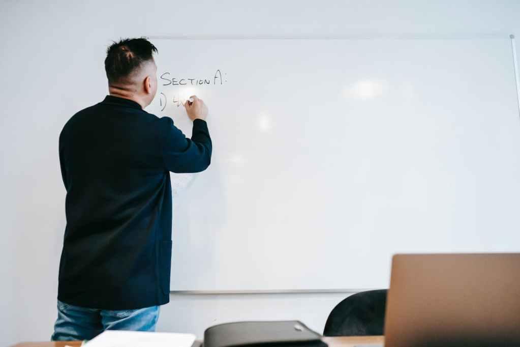 photo of man writing on whiteboard