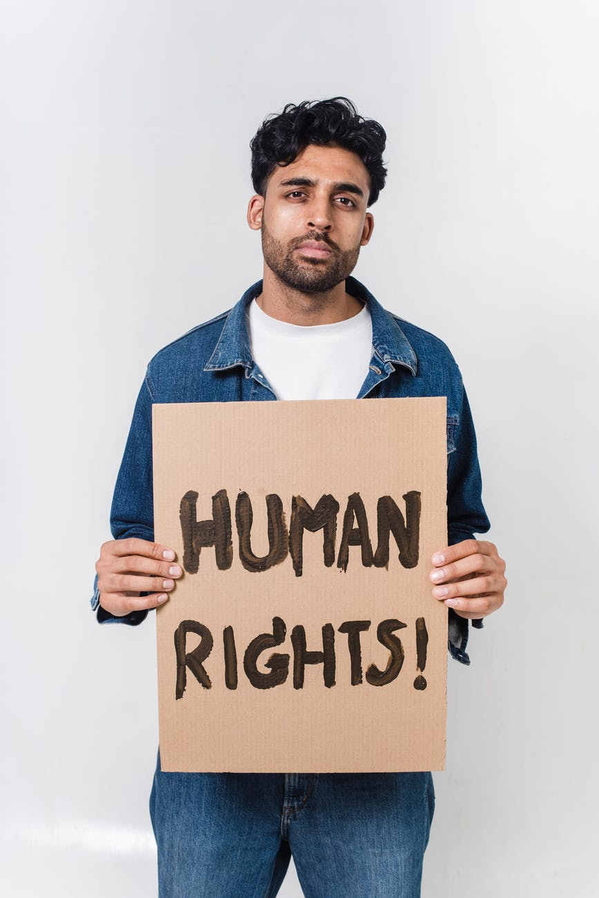 man in blue and white long sleeve shirt holding human rights text