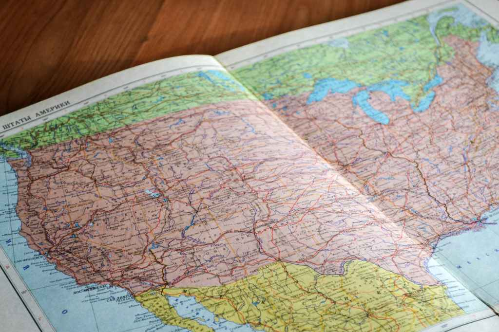 map of the world book laid open on brown wooden surface