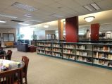 The circulation desk is gone - replaced by the fiction shelves and leather seating. I painted the columns crimson to add a little drama.