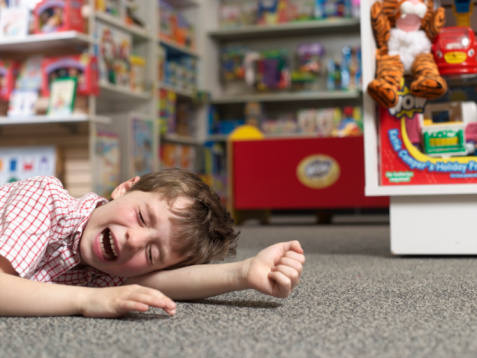 Child having tantrum in store and crying on the floor
