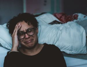 Woman with dark, curly hair wearing dark glasses holds her forehead and cries next to her unmade bed.