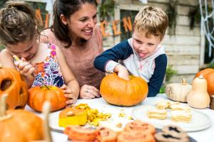 A smiling mother helps her daughter and son carve pumpkins at a table covered in Halloween treats.