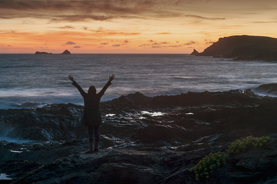 Image of a person standing arms outstretched at sunset by the water